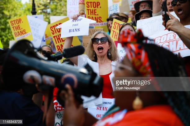 A woman holds a clothes hanger with a sign that says stop the bans during a protest against recently passed abortion ban bills at the Georgia State...