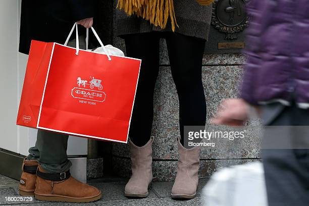 Woman holds a Coach Inc. Shopping bag in the Ginza district of Tokyo, Japan, on Friday, Jan. 25, 2013. Japan's consumer prices fell for the seventh...