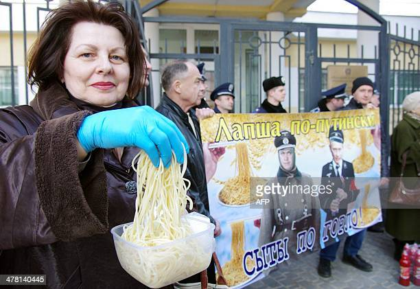 """Woman holds a container with noodles in front of a placard portraying Russian President Vladimir Putin as a German SS officer and reading """"Putin's..."""