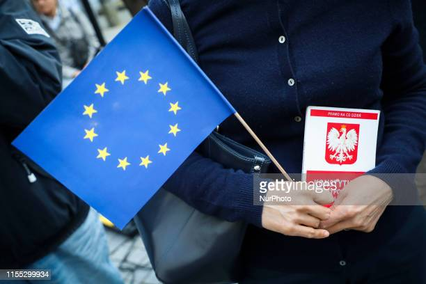 A woman holds a copy of the Polish Constitution and EU flag during a protest in front of district court to support the national prosecutor on Mariusz...