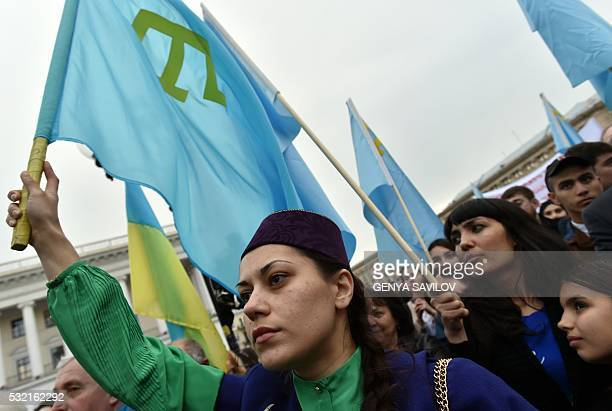A woman holds a Crimean Tatar flag during a memorial ceremony on the Independence square in Kiev on May 18 2016 in commemoration of the 72nd...