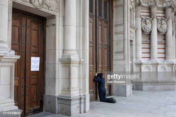 Woman holds a cross and prays in front of a closed Westminster Cathedral on April 12, 2020 in London, England. As the lockdown continues due to the...