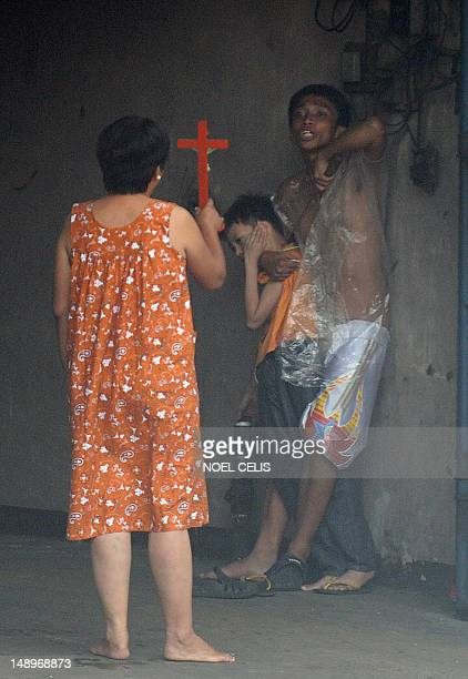 A woman holds a cross towards hostage taker Remer Parparan as he points an icepick at 10 years old Jason Pineda during a hostage taking incident in...