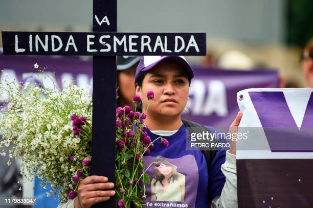 A woman holds a cross with the name of a murdered relative during a protest against femicides in Mexico City on November 3 2019