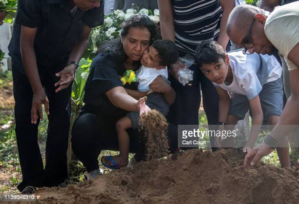 A woman holds a crying child as she throws earth onto a coffin during a funeral for a person killed in the Easter Sunday attack on St Sebastian's...