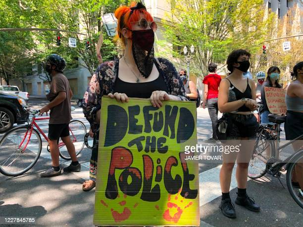 """Woman holds a """"Defund the Police"""" sign in Portland, Oregon on July 30, 2020. - Police in Portland cleared parks and nearby roads in the downtown area..."""