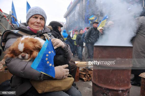 A woman holds a dog and the EU and Ukrainian flags as she sits in a protest camp during a mass opposition rally at Independence Square in Kiev on...