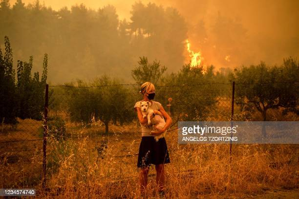 Woman holds a dog in her arms as forest fires approach the village of Pefki on Evia island, Greece's second largest island, on August 8, 2021. -...