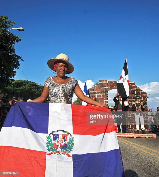 A woman holds a Dominican national flag during a carnival parade in Santo Domingo on March 6 2011 AFP PHOTO / ERIKA SANTELICES