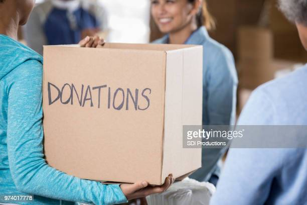 Woman holds a donation box during food and clothing drive