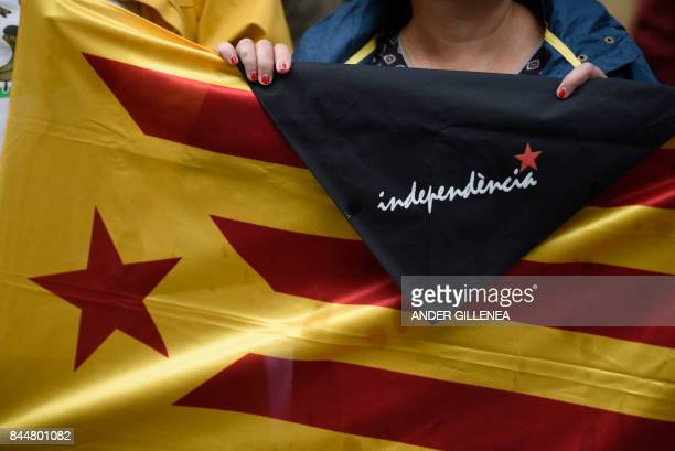 A woman holds a Estelada and a kerchief reading independence during a demonstration to support the Catalan referendum for October 1 in the Spanish...