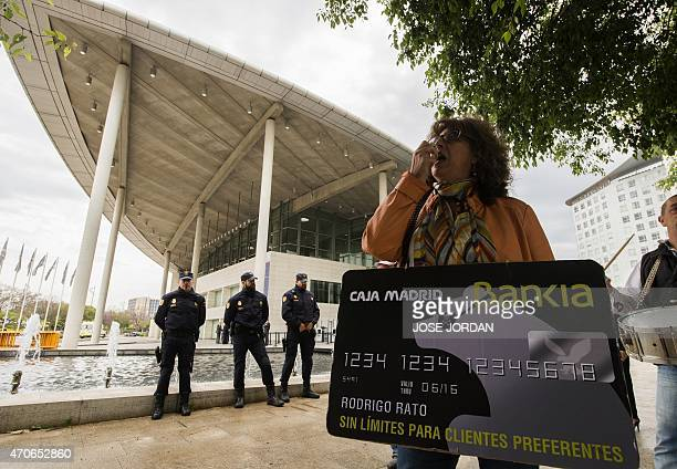 A woman holds a fake Bankia credit card of Rodrigo Rato as she protests against fraud outside the building where is held the Bankia Shareholders...