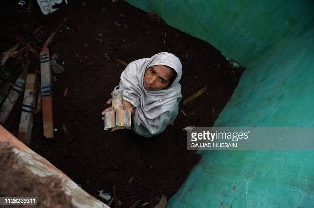 A woman holds a fin of an exploded mortar that locals say was fired by Pakistani troops damaging her house in Patri village in India's Mendhar near...
