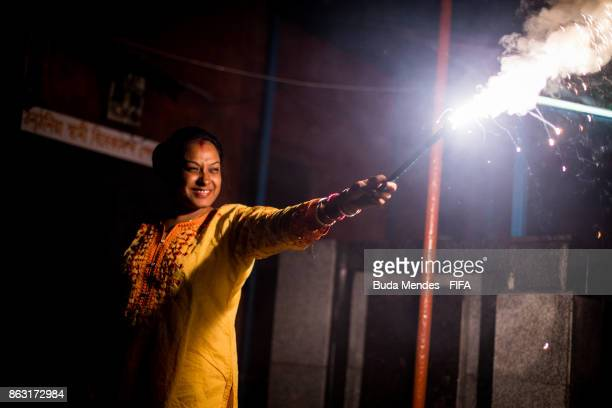 A woman holds a firecracker while celebrating the Hindu festival of Diwali the annual festival of lights in India during of the FIFA U17 World Cup...