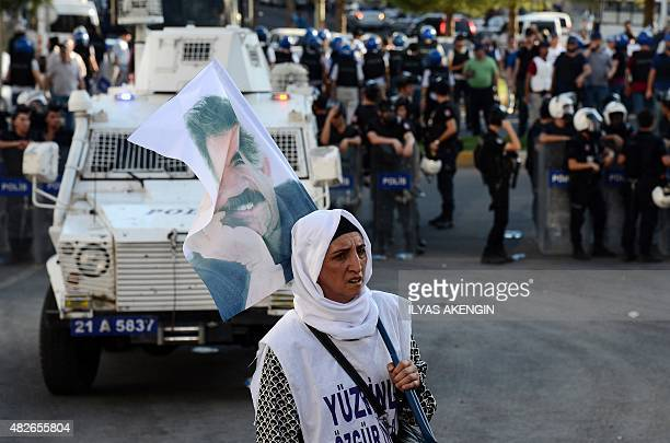 A woman holds a flag of jailed Kurdish leader Abdullah Ocalan as she stands opposite Turkish riot police in Diyarbakir on August 1 2015 during a...
