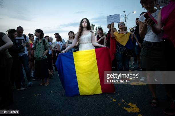 TOPSHOT A woman holds a flag of Romania during a gathering in front of the Romanian Prime Minister's office building on June 21 2018 in Bucharest...