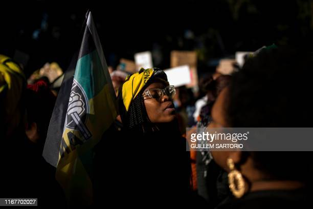 A woman holds a flag of the South African ruling party African National Congress in front of the Johannesburg Stock Exchange during a protest against...
