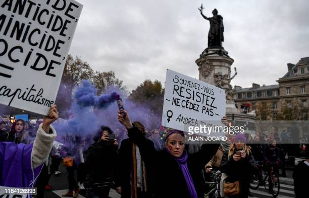 "Woman holds a flare and a placard reading ""Remember, resist, do not give in"" during a protest to condemn violence against women, on November 23 in..."