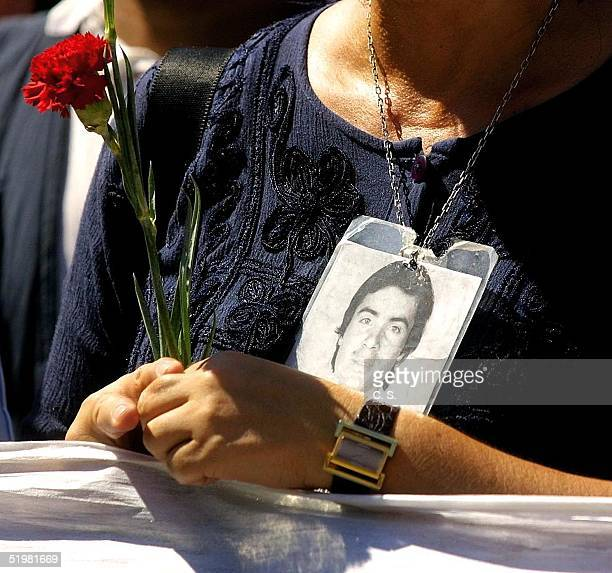 A woman holds a flower and the photo of a disappeared relative during a march organized by human rights organizations in the region of Barriga where...