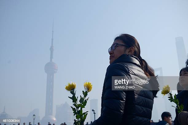 A woman holds a flower bouquet as she prepares to pray for victims of the New Year's stampede in Shanghai on January 4 2015 New Year revellers had...