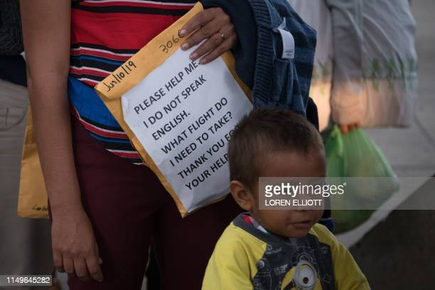 Woman holds a folder with a sentence written in English to help her find her way as Central American migrant families recently released from federal...