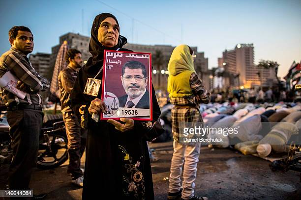 Woman holds a framed campaign poster as supporters of Mohamed Morsi, the Muslim Brotherhood's presidential candidate, pray during a protest against...