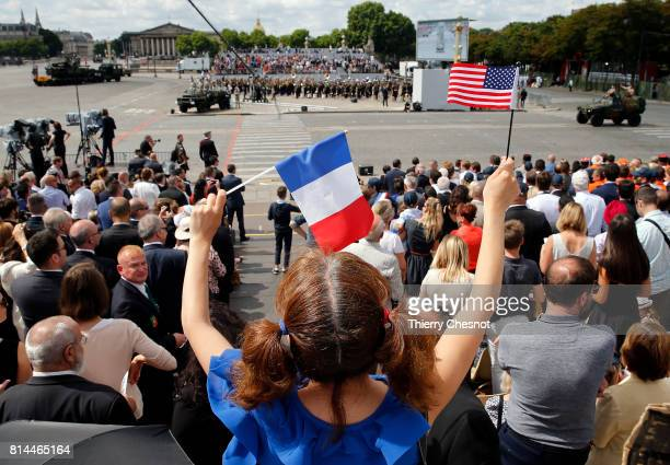A woman holds a French flag and an American flag during the traditional Bastille day military parade on the ChampsElysees on July 14 2017 in Paris...