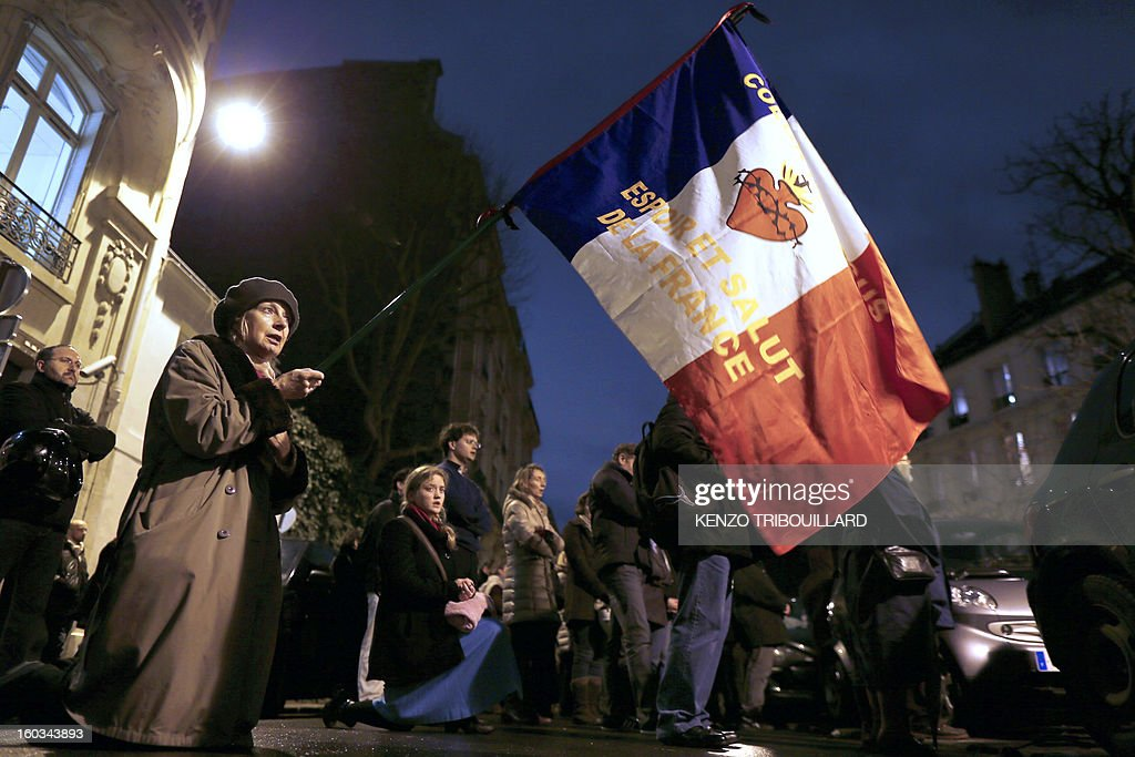 A woman holds a French flag during a protest organized by fundamentalist Christians group Civitas Institute against same-sex marriage on January 29, 2013 in Paris. France's Parliament began today examining draft legislation on same-sex marriage after months of rancorous debate and huge street protests by both supporters and opponents.
