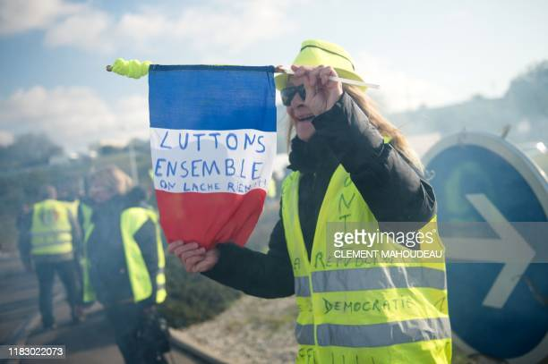 """Woman holds a French Flag reading """"Let's fight together"""" as members of the """"yellow vest"""" movement block the """"Plan de Campagne"""" mall in Cabries, near..."""