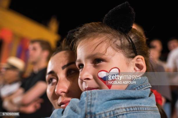 A woman holds a girl with a Russian flag shaped as a heart painted on her left cheek as they watch the Russia 2018 World Cup Group D football match...