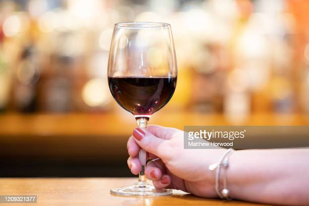 A woman holds a glass of red wine in a pub on February 28 2020 in Cardiff Wales A new law setting a minimum alcohol price will come into force on...