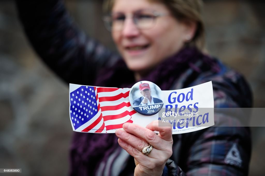 A woman holds a 'God Bless America' sticker during a demonstration in Lake Oswego, Ore., on March 4, 2017, on a day of nationwide solidarity for President Trump. Hundreds marched through the streets outnumbered by counter-demonstrators.