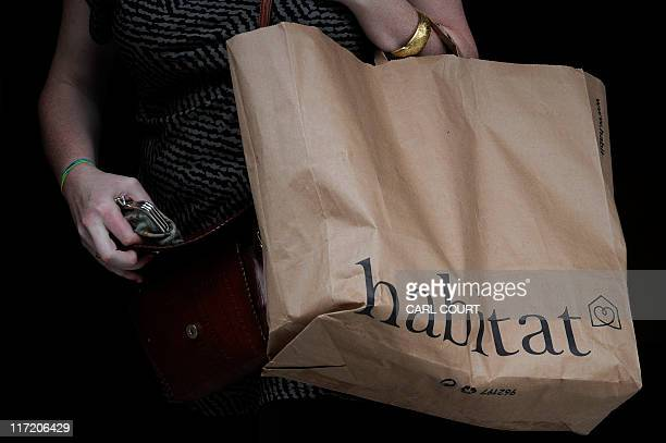 A woman holds a Habitat bag as she leaves the store in central London on June 24 2011 Britain's Home Retail Group on Friday said it had bought the...