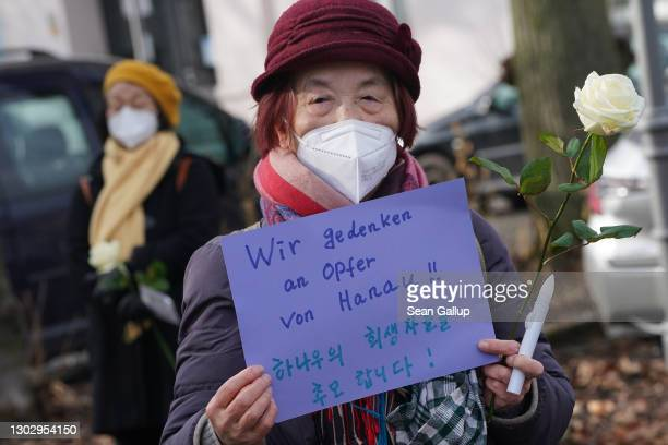 """Woman holds a hand-written sign that reads: """"We commemorate the victims of Hanau!"""" with additional text in Korean at a small gathering to commemorate..."""