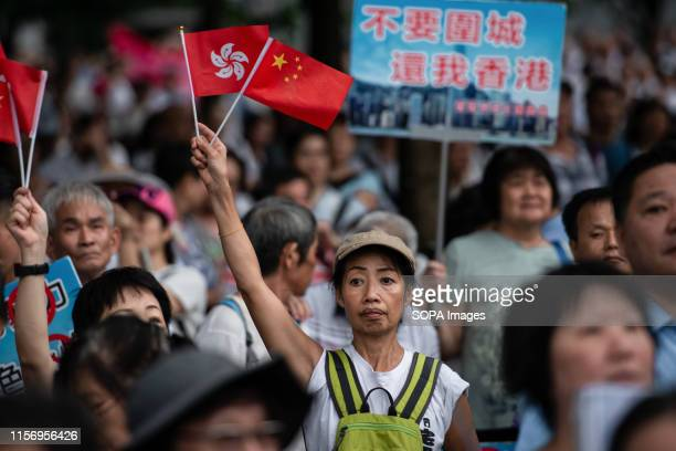A woman holds a Hong Kong and Chinese flags while participating of progovernment Safeguard Hong Kong rally at Tamar Park Government supporters show...