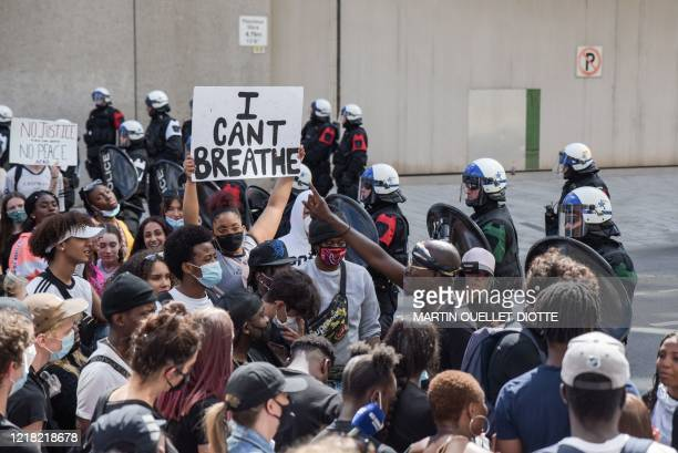"""Woman holds a """"I Can't Breathe"""" sign as Montreal Police and protesters face off during a march against police brutality and racism in Montreal,..."""