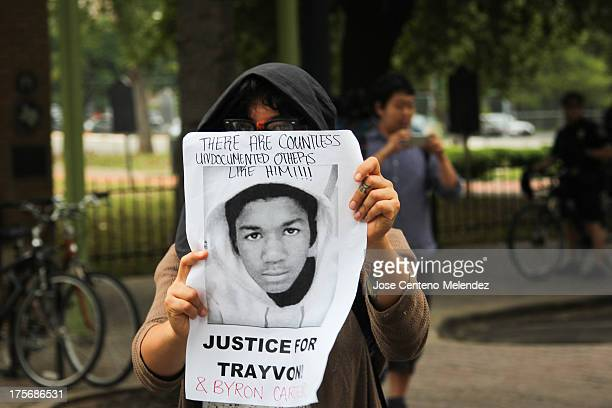 """Woman holds a """"Justice for Trayvon"""" poster during a protest in response to the acquittal of George Zimmerman in the Trayvon Martin murder trial."""