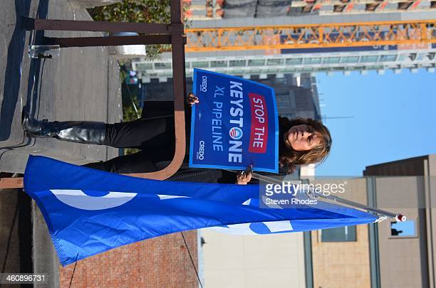 CONTENT] A woman holds a Keystone XL protest sign and 350org flag on the roof of a six story apartment building across from the SF Jazz Center where...