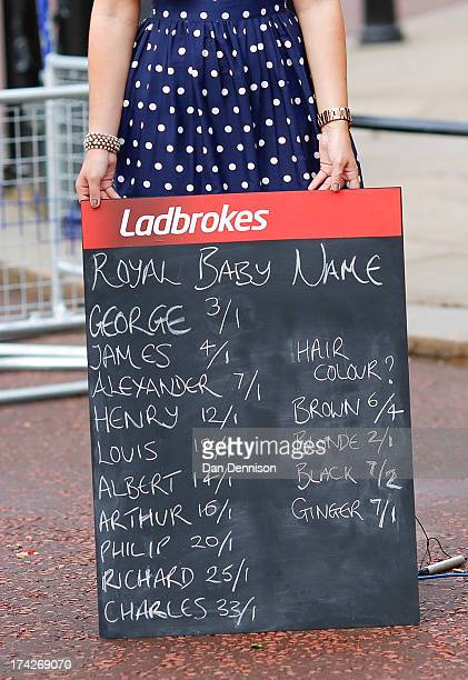 A woman holds a Ladbrokes board listing possible baby names to bet on as media gather outside Buckingham Palace to read the easel displaying the...
