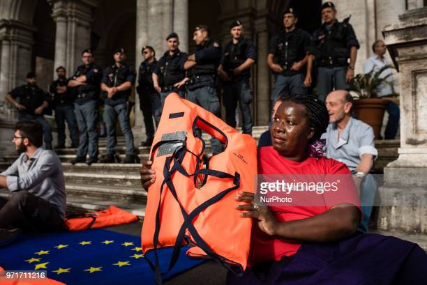 A woman holds a life jacket during a rally in Rome Italy on June 11 2018 against Italian government decision to block ports to a German NGO ship with...