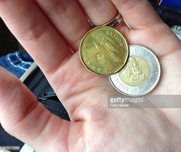 A woman holds a 'loonie' and 'toonie' of Canadian currency