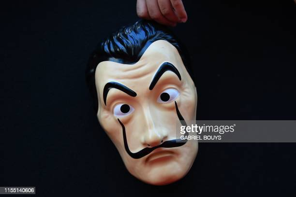A woman holds a mask of the Spanish TV show La Casa de Papel before a photocall for the presentation of the third season of the show in Madrid on...