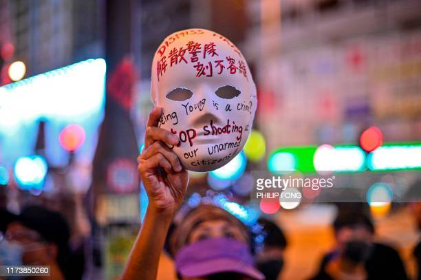 TOPSHOT A woman holds a mask with slogans written on as protesters gather outside Mong Kok police station in Hong Kong on October 5 a day after the...
