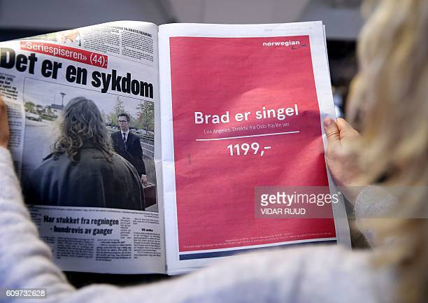 A woman holds a newspaper with an advertising of Norwegian Airlines reading 'Brad is single Los Angeles direct from Oslo one way' in Oslo on...