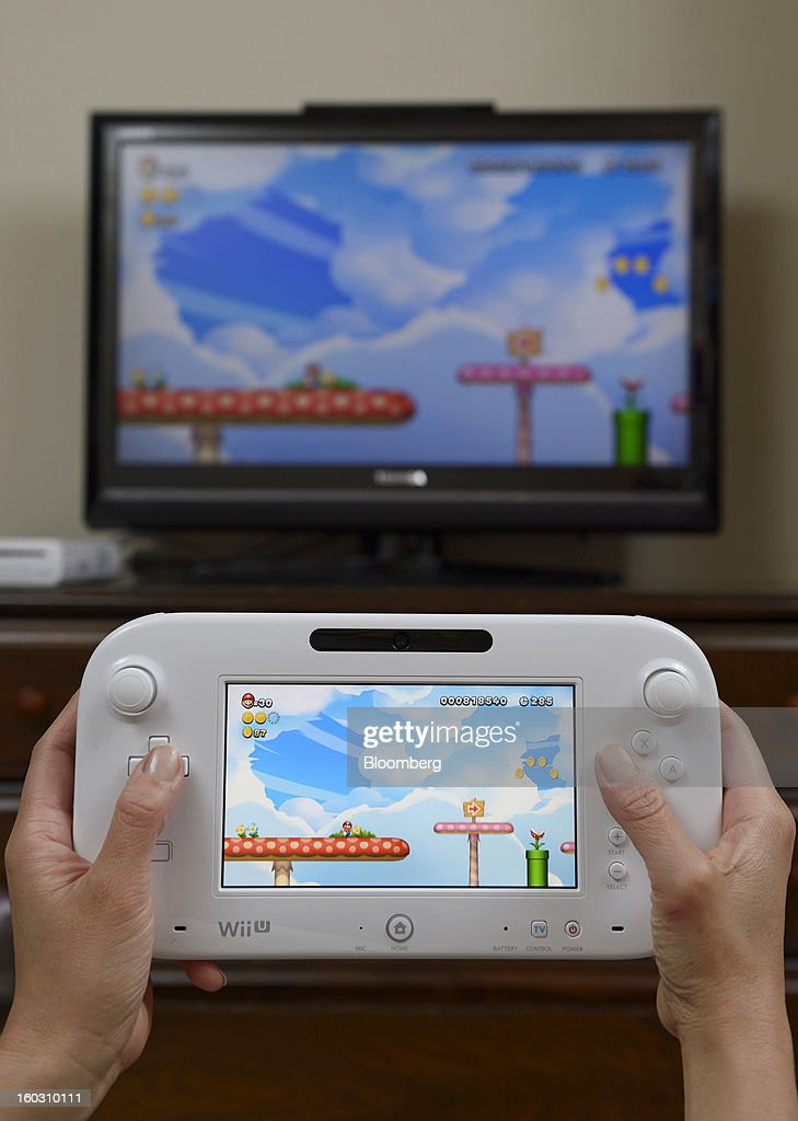 A Woman holds a Nintendo Co. Wii U touch-screen controller displaying the new Super Mario Bros. U game in this arranged photograph in Kawasaki City, Kanagawa Prefecture, Japan, on Sunday, Jan. 27, 2013. Sony Corp. and Nintendo Co., Japan's biggest makers of gaming devices, rose after China Daily said the world's most-populous country may end a 12-year ban on the sale of video-game consoles. Nintendo, the creator of Super Mario, added 3.4 percent to 9,630 yen, the highest since Dec. 7, in Osaka. Photographer: Akio Kon/Bloomberg via Getty Images