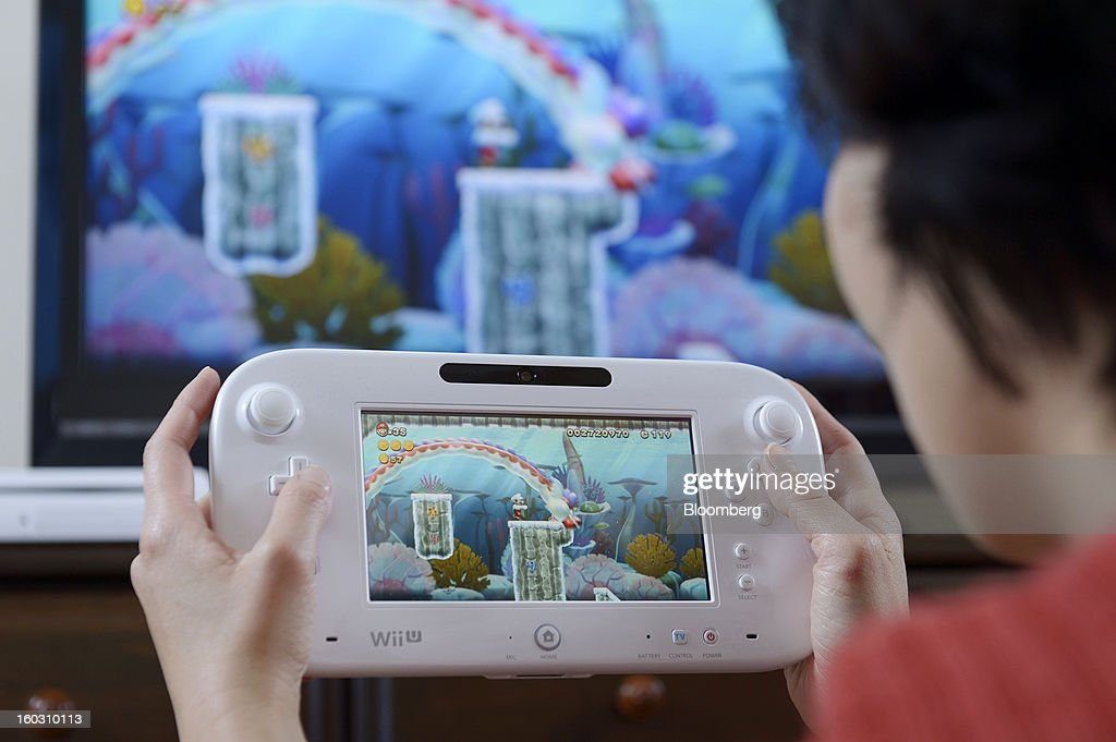 A woman holds a Nintendo Co. Wii U touch-screen controller displaying the new Super Mario Bros. U game in this arranged photograph in Kawasaki City, Kanagawa Prefecture, Japan, on Tuesday, Jan. 29, 2013. Sony Corp. and Nintendo Co., Japan's biggest makers of gaming devices, rose after China Daily said the world's most-populous country may end a 12-year ban on the sale of video-game consoles. Nintendo, the creator of Super Mario, added 3.4 percent to 9,630 yen, the highest since Dec. 7, in Osaka. Photographer: Akio Kon/Bloomberg via Getty Images
