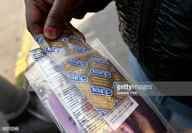 A woman holds a packet of condoms and a sexual transmitted disease informational packet she received February 17 2005 from a mobile health van from...