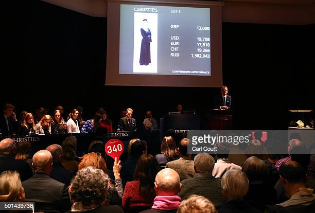 A woman holds a paddle to bid for a Midnight Blue Velvet Wedding Ensemble during the auction for items belonging to late British Prime Minister...