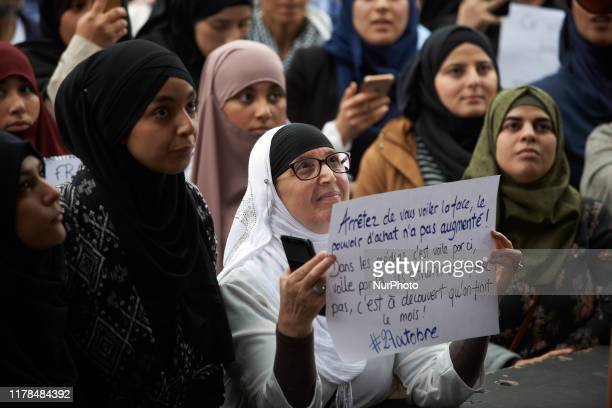 Woman holds a paper reading 'Stop veiling your face, purchasing power isn't rising up. In medias, it's headscarf here, headscarf there but we don't...