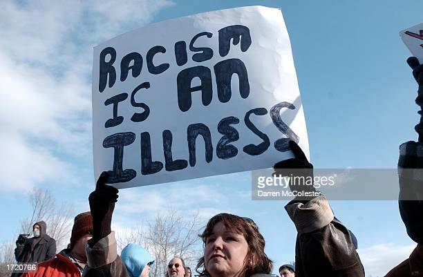 A woman holds a peace sign while protesting at a NeoNazi rally held by supporters of the World Church of the Creator January 11 2002 in Lewiston...